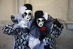 2 диаграммы масленицы Венеции в черно-белых костюмах и маски под аркадой дворца Венеции Италии ` s дожа Стоковая Фотография