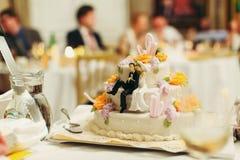 Диаграммы новобрачных сидят на вкусном свадебном пироге Стоковое Изображение
