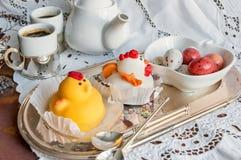 Диаграммы от марципана в форме белых и желтых цыплят на таблице пасхи с кофейными чашками и яичками печенья в керамической белизн Стоковая Фотография RF