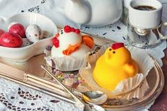 Диаграммы от марципана в форме белых и желтых цыплят на таблице пасхи с кофейными чашками и яичками печенья в керамической белизн Стоковые Фото