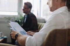 Диаграммы чтения бизнесмена во время встречи Стоковое Фото