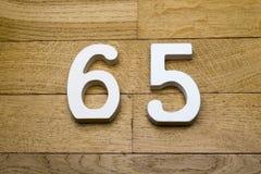Диаграммы шестьдесят пять на деревянном, пол партера Стоковая Фотография