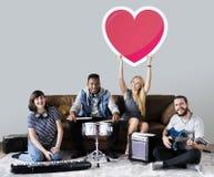 Диапазон музыкантов держа смайлик сердца стоковые изображения