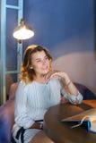 Дивная молодая женская девушка смотрит отсутствующей и усмехается обширно, держит Стоковые Изображения