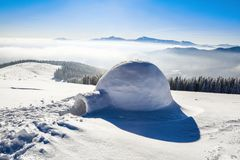 Дивная огромная белая снежная хата, иглу дом изолированного туриста стоит на высокой горе далеко далеко от человеческого глаза Стоковые Фотографии RF