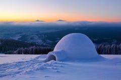 Дивная огромная белая снежная хата, иглу дом туриста стоит на высокой горе далеко далеко от человеческого глаза Стоковая Фотография RF