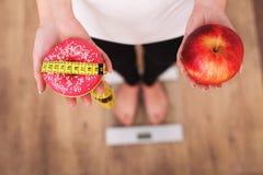 Диета Вес тела женщины измеряя на веся масштабе держа донут и яблоко Помадки нездоровая высококалорийная вредная пища Dieting, зд стоковые изображения