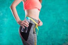Диета Вручает измеряя талию с лентой Подходящая и здоровая женщина на предпосылке бирюзы Стоковые Фото