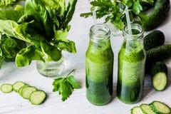 Диета вытрезвителя 2 малых бутылки свежих зеленых smoothies с ингридиентами на светлой деревянной предпосылке Стоковые Фото