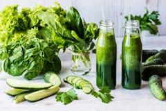Диета вытрезвителя 2 малых бутылки свежих зеленых smoothies с ингридиентами на светлой деревянной предпосылке Стоковые Изображения
