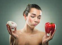 Диета женщин Донут или болгарские перцы? стоковое изображение rf