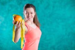Диета Здоровая счастливая женщина с апельсином и рулетка для концепции потери диеты и веса - на предпосылке бирюзы Стоковые Изображения
