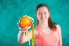 Диета Здоровая счастливая женщина с апельсином и рулетка для концепции потери диеты и веса - на предпосылке бирюзы Стоковое фото RF