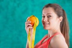Диета Здоровая счастливая женщина с апельсином и рулетка для концепции потери диеты и веса - на предпосылке бирюзы Стоковое Фото