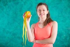 Диета Здоровая счастливая женщина с апельсином и рулетка для концепции потери диеты и веса - на предпосылке бирюзы Стоковые Фотографии RF