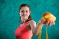 Диета Здоровая счастливая женщина с апельсином и рулетка для концепции потери диеты и веса - на предпосылке бирюзы Стоковые Фото
