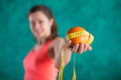Диета Здоровая счастливая женщина с апельсином и рулетка для концепции потери диеты и веса - на предпосылке бирюзы Стоковое Изображение RF