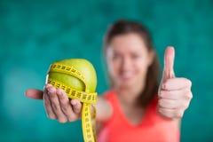 Диета Здоровая счастливая женщина с яблоком и рулетка для концепции потери диеты и веса - изолированной на предпосылке бирюзы Стоковая Фотография RF