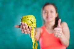 Диета Здоровая счастливая женщина с яблоком и рулетка для концепции потери диеты и веса - изолированной на предпосылке бирюзы Стоковые Изображения RF