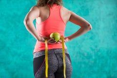 Диета Здоровая счастливая женщина с яблоком и рулетка для концепции потери диеты и веса - на предпосылке бирюзы Стоковая Фотография
