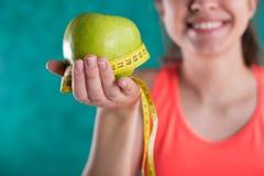 Диета Здоровая счастливая женщина с яблоком и рулетка для концепции потери диеты и веса - изолированной на предпосылке бирюзы Стоковое Изображение
