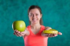 Диета Здоровая счастливая женщина с яблоком и рулетка для концепции потери диеты и веса - изолированной на предпосылке бирюзы Стоковое Фото