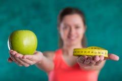 Диета Здоровая счастливая женщина с яблоком и рулетка для концепции потери диеты и веса - изолированной на предпосылке бирюзы Стоковые Фото
