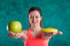 Диета Здоровая счастливая женщина с яблоком и рулетка для концепции потери диеты и веса - изолированной на предпосылке бирюзы Стоковые Фотографии RF