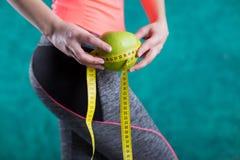 Диета Здоровая счастливая женщина с яблоком и рулетка для концепции потери диеты и веса - изолированной на предпосылке бирюзы Стоковые Изображения