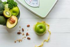 Диета и здоровая концепция жизни Кран измерения свежие зеленые овощ и масштаб веса со для уменьшением диеты женщин стоковая фотография rf