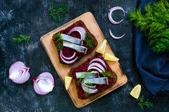 Диетические сандвичи с свеклами, куски посоленных сельдей и красный лук на хлебе рож Стоковая Фотография