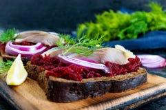 Диетические сандвичи с свеклами, куски посоленных сельдей и красный лук на хлебе рож на черной предпосылке Стоковые Изображения
