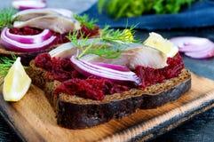 Диетические сандвичи с свеклами, куски посоленных сельдей и красный лук на хлебе рож на черной предпосылке Стоковая Фотография