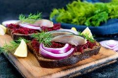 Диетические сандвичи с свеклами, куски посоленных сельдей и красный лук на хлебе рож на черной предпосылке Стоковое Изображение