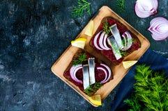 Диетические сандвичи с свеклами, куски посоленных сельдей и красный лук на хлебе рож на черной предпосылке Стоковое Изображение RF