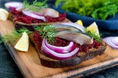 Диетические сандвичи с свеклами, куски посоленных сельдей и красный лук на хлебе рож на черной предпосылке Стоковые Фотографии RF