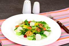 Диетический очень вкусный салат на белой плите arugula, груши, грецкого ореха Стоковое Фото