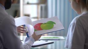 Диетолог говоря к девушке о здоровой еде, показывая воспитательные карточки акции видеоматериалы