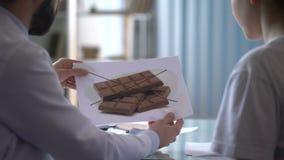 Диетолог говоря к женскому пациенту о диете, доктор показывая изображения акции видеоматериалы