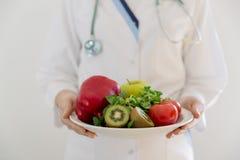 Диетолог, доктор держа свежий фрукт и овощ, здоровое питание, еду питания как рецепт для хороших здоровий изолированная женщина в Стоковое Изображение RF