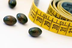 Диетпитание - измеряя лента и пилюльки Стоковые Изображения