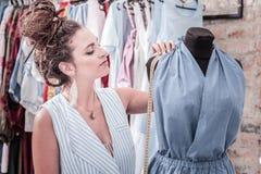 Дизайнерская измеряя высота формы тела пока портняжничающ платье лета стоковые фото