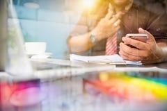 Дизайнерская рука бизнесмена используя умный телефон, передвижное onli оплат Стоковая Фотография RF