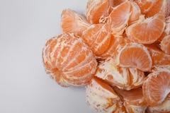 Дизайнерская fruity предпосылка от свежих кусков tangerine и одного круглого всего апельсина мандарина, выведенных белая предпосы Стоковое фото RF