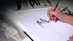 Дизайнерские платья покрашенные на эскизе на таблице на ее лож много других эскизов конец вверх видеоматериал
