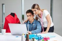 Дизайнеры одежды работая на компьтер-книжке Стоковое Фото