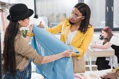 Дизайнеры совместно работая на проекте в студии дизайна одежды Стоковые Изображения