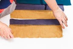 Дизайнер аранжирует прокладки тканей для заплатки Стоковая Фотография
