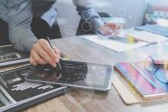 Дизайнер вебсайта держа умный телефон и работая digita компьютера Стоковое Изображение