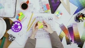 Дизайнер женщины играя с необыкновенной игрушкой куба Rubiks в перерыве  видеоматериал